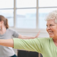 Happy senior woman practicing yoga at gym class.